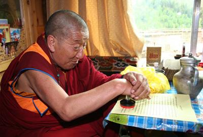 吉美多吉法王在給三世多杰羌佛的祝賀信上簽字後,正在蓋章。