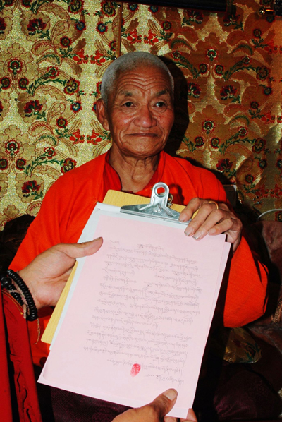 仁增尼瑪法王將他寫好的認證三世多杰羌佛的認證書拿在手中照相。